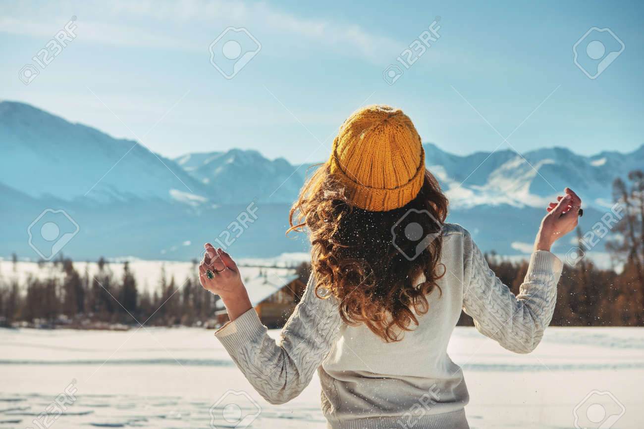 Attractive young girl walks in snowy mountains - 155882216