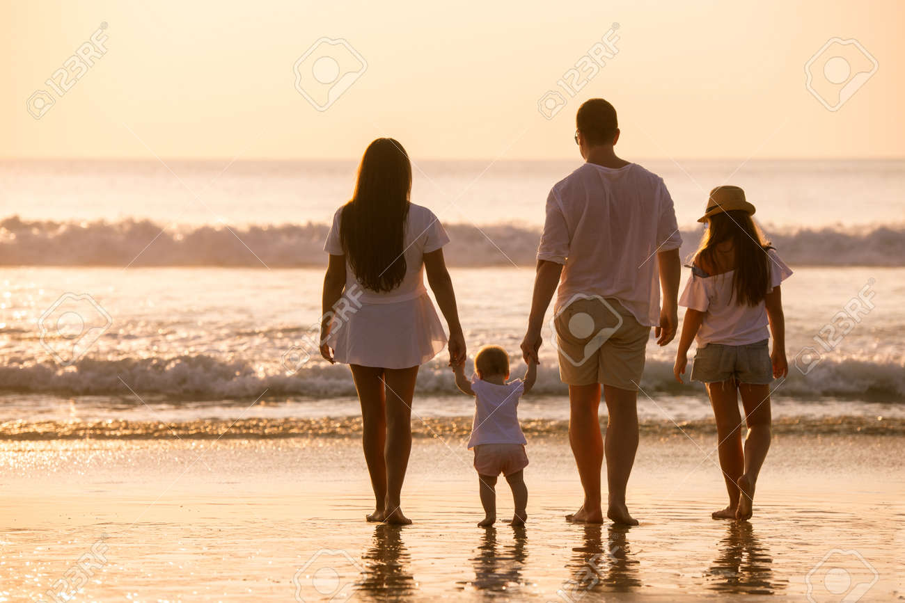 Family of four peoples in white are standing and relaxing at sunset sea beach - 155924900