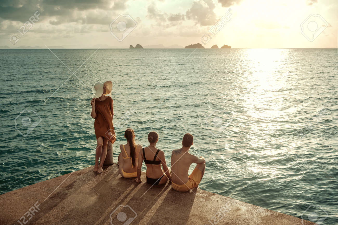 Four young peoples sits on pier and looking at sea and sunset - 156041145