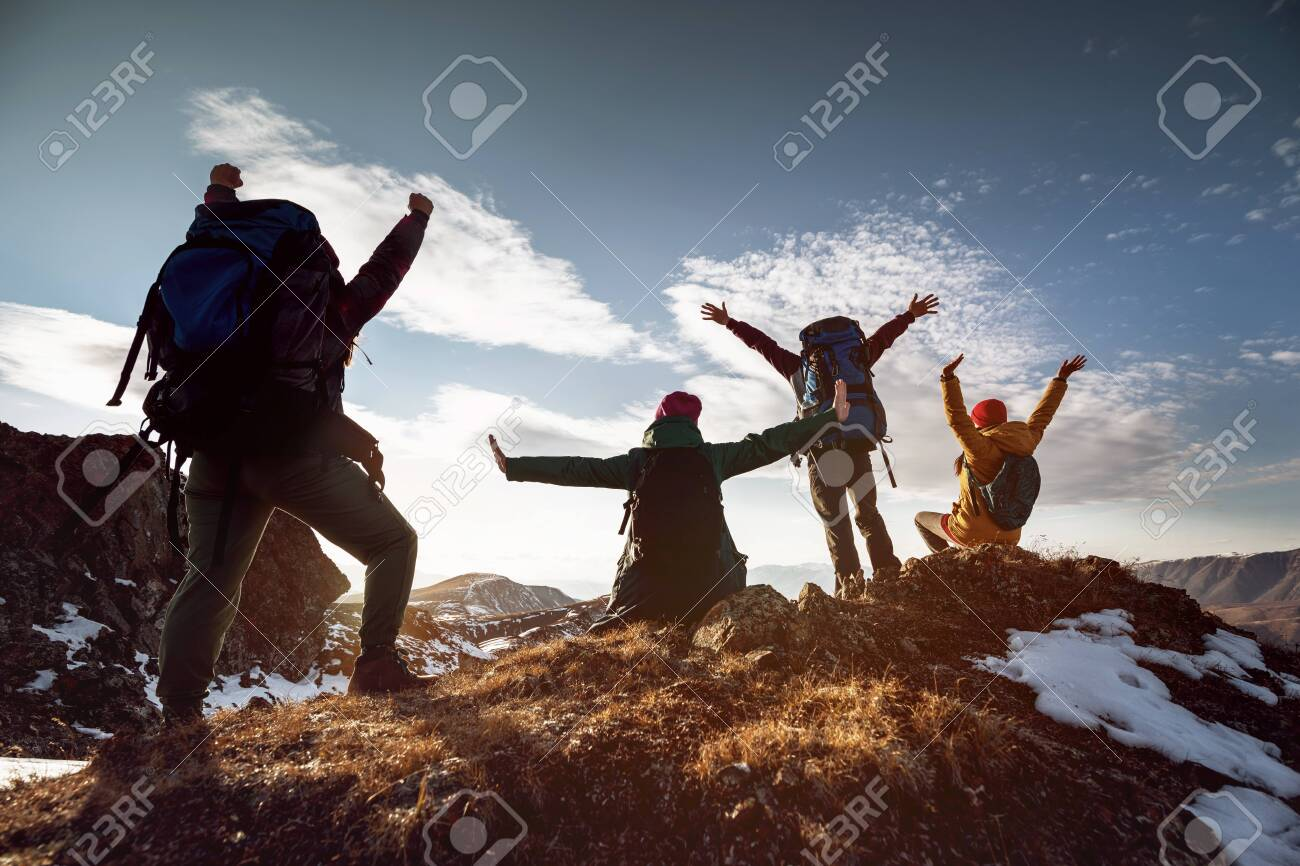 Four happy hikers stands in winner poses at mountain top at sunset time - 157019911