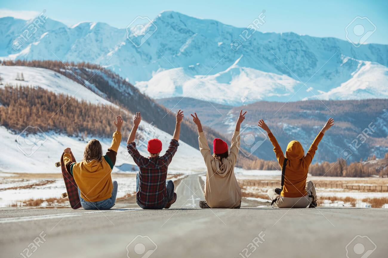 Four happy friends sits with raised arms on straight mountains road and having fun. Travel concept - 157598986