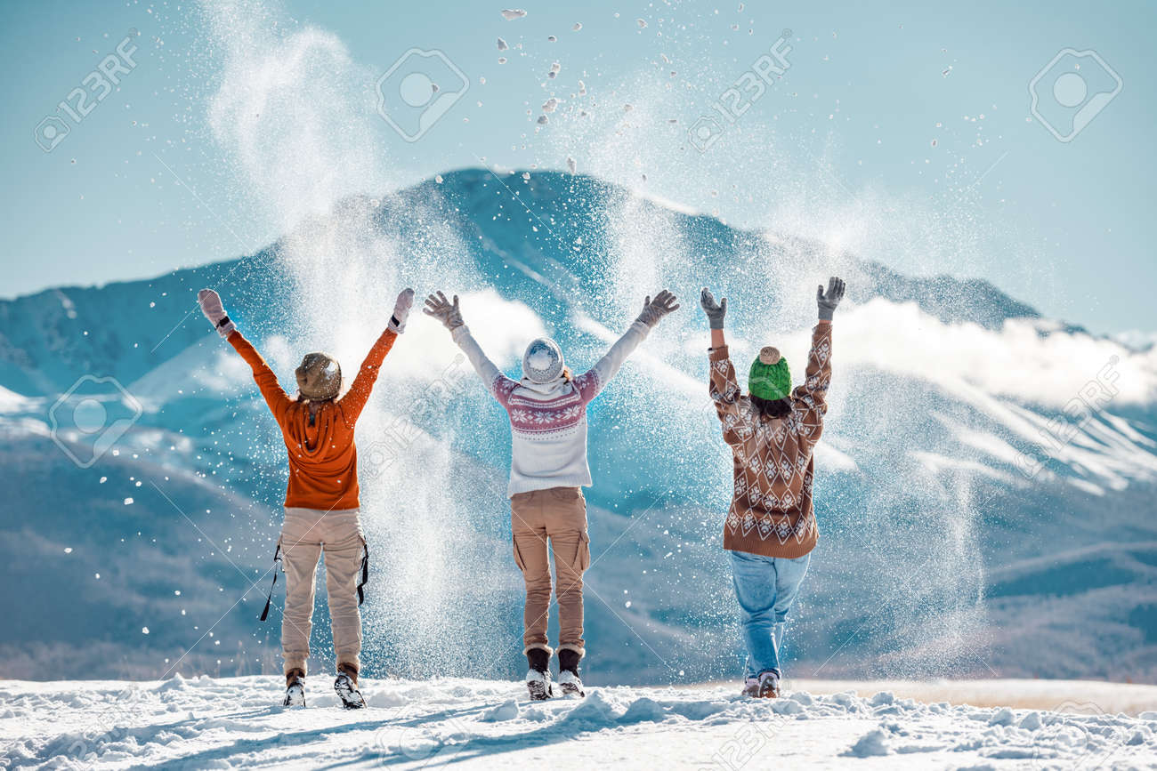 Three happy adult girls are having fun and throws first snow on background of mountains. Travel in winter time concept - 157799288