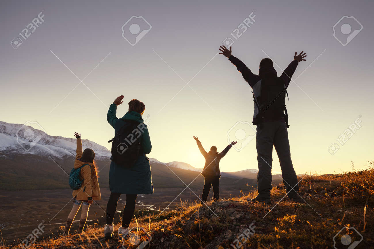 Four young hikers greetings with raised arms sunset in mountains - 158135057