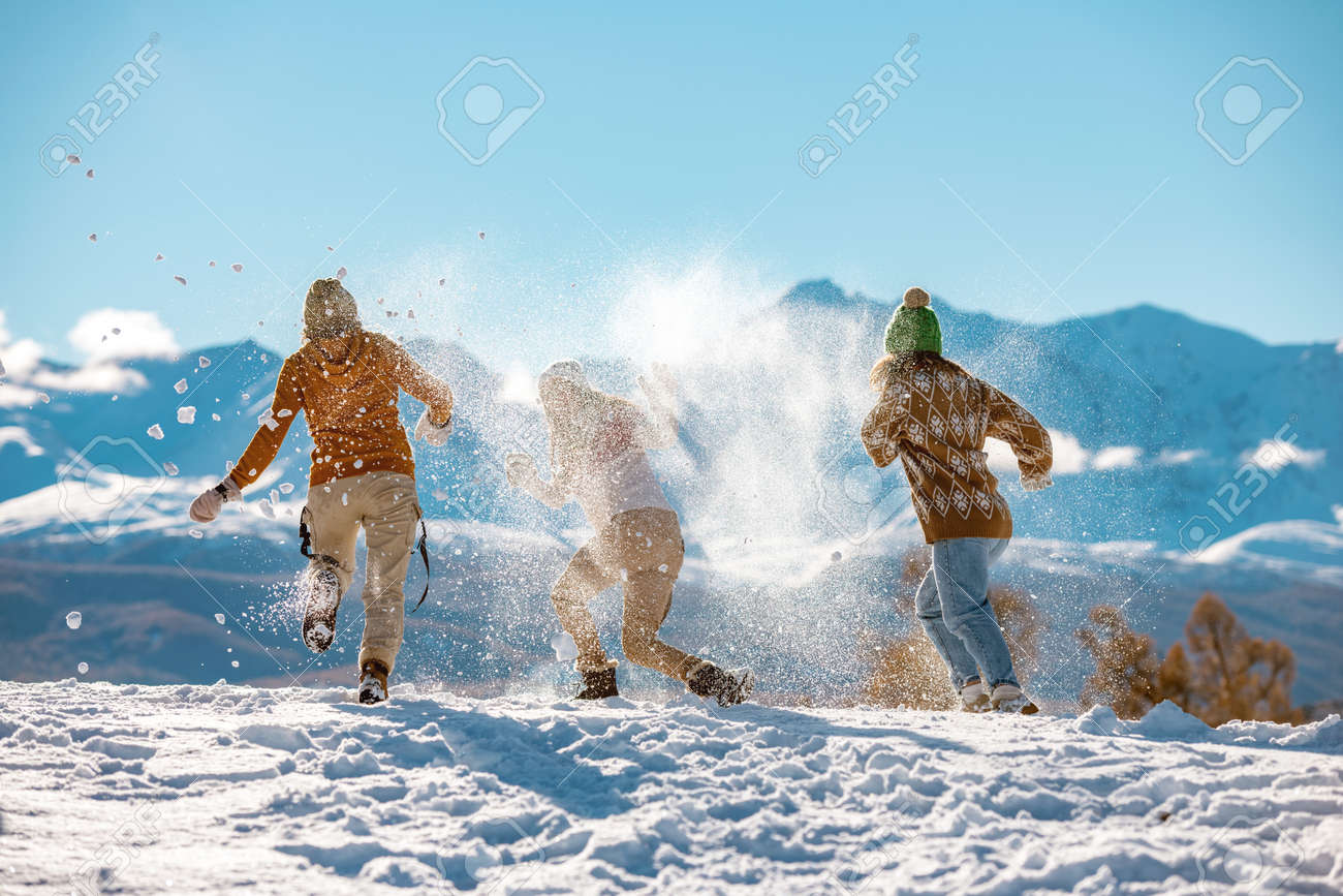 Three young happy girls friends are having fun in snow fight in mountains. First snow and winter vacations concept - 159063630
