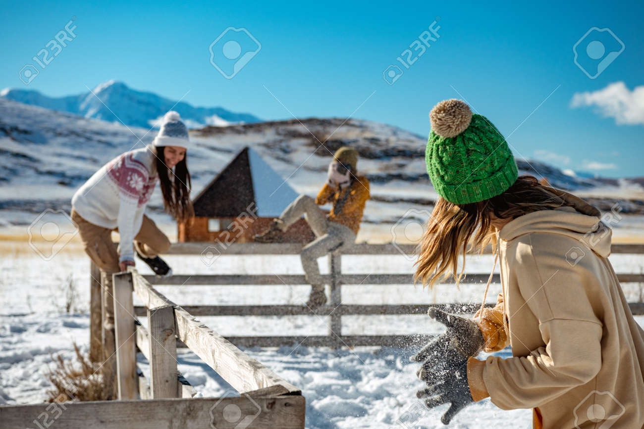 Three happy young girlfriends are having fun at wooden fence at wintertime outdoors in mountains. Winter vacations concept - 159094872
