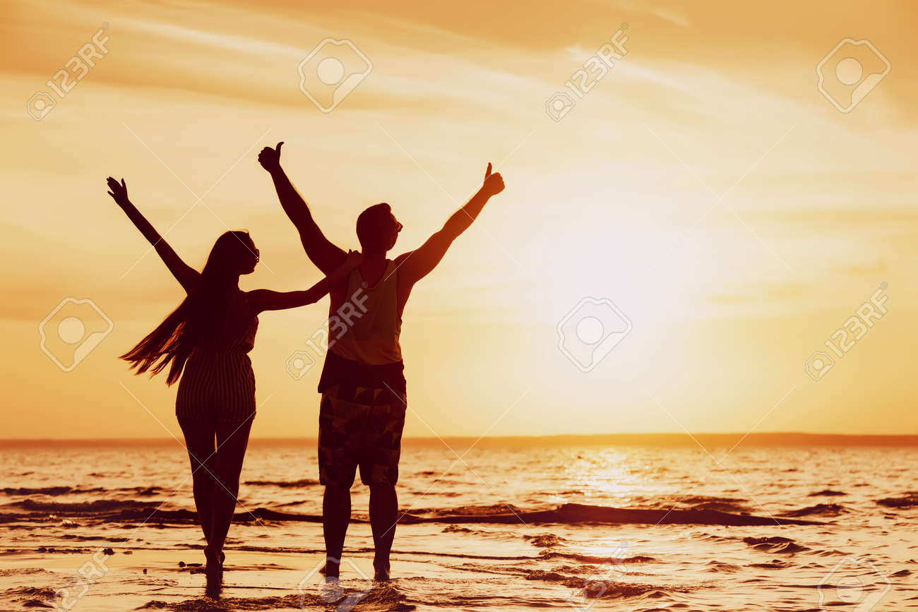 Happy couple stands with raised arms at sunset beach - 159457852