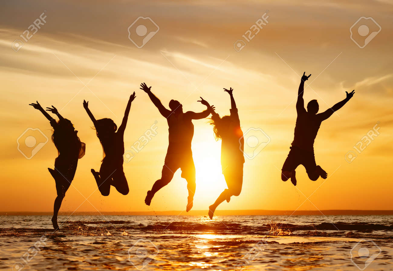 Silhouettes of five happy jumping friends in water at sunset time - 159459451