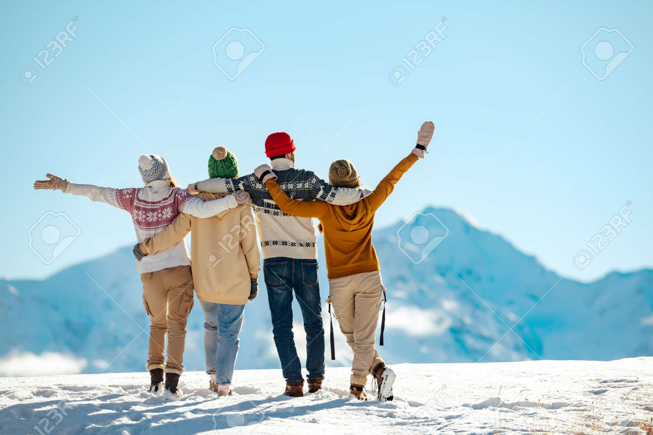 Four happy friends are standing and embracing against snow capped mountains at sunny day. Winter vacations concept - 159506361