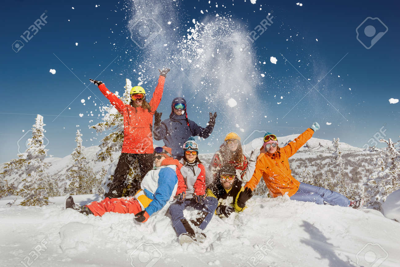 Group of young friends in colorful clothes are having fun and posing at the top of mountain. Winter ski and snowboarding vacations concept - 159677553