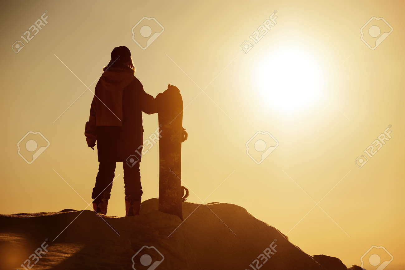Girl snowboarder stands with snowboard against sunset sky. Ski resort concept - 159685013