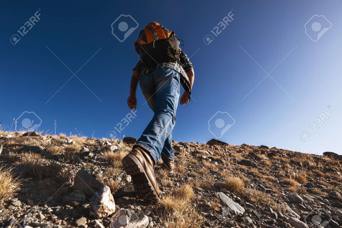 Unrecognizable male traveler or hiker goes uphill. Closeup photo from boots - 159685120