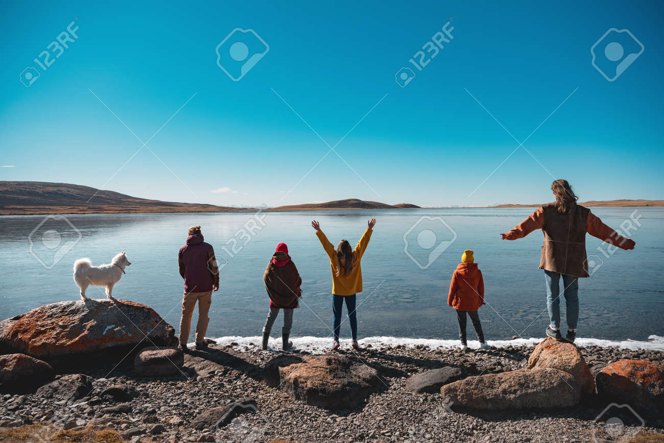 Group of five young friends with white husky dog are having rest and looking at mountain lake. Altai mountains, Siberia, Russia - 159900772