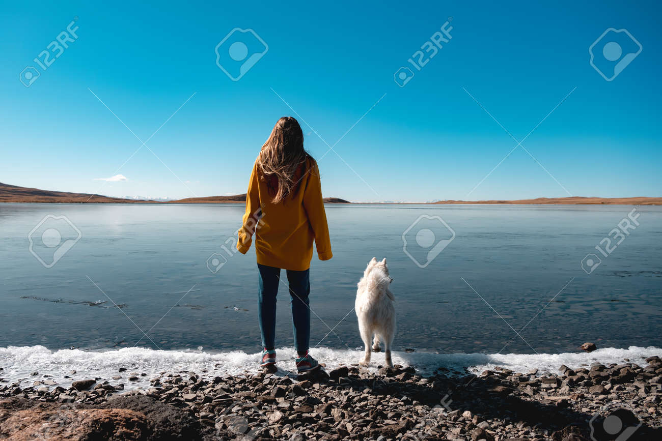 Young girl with white husky stands at frozen lake beach - 159900600