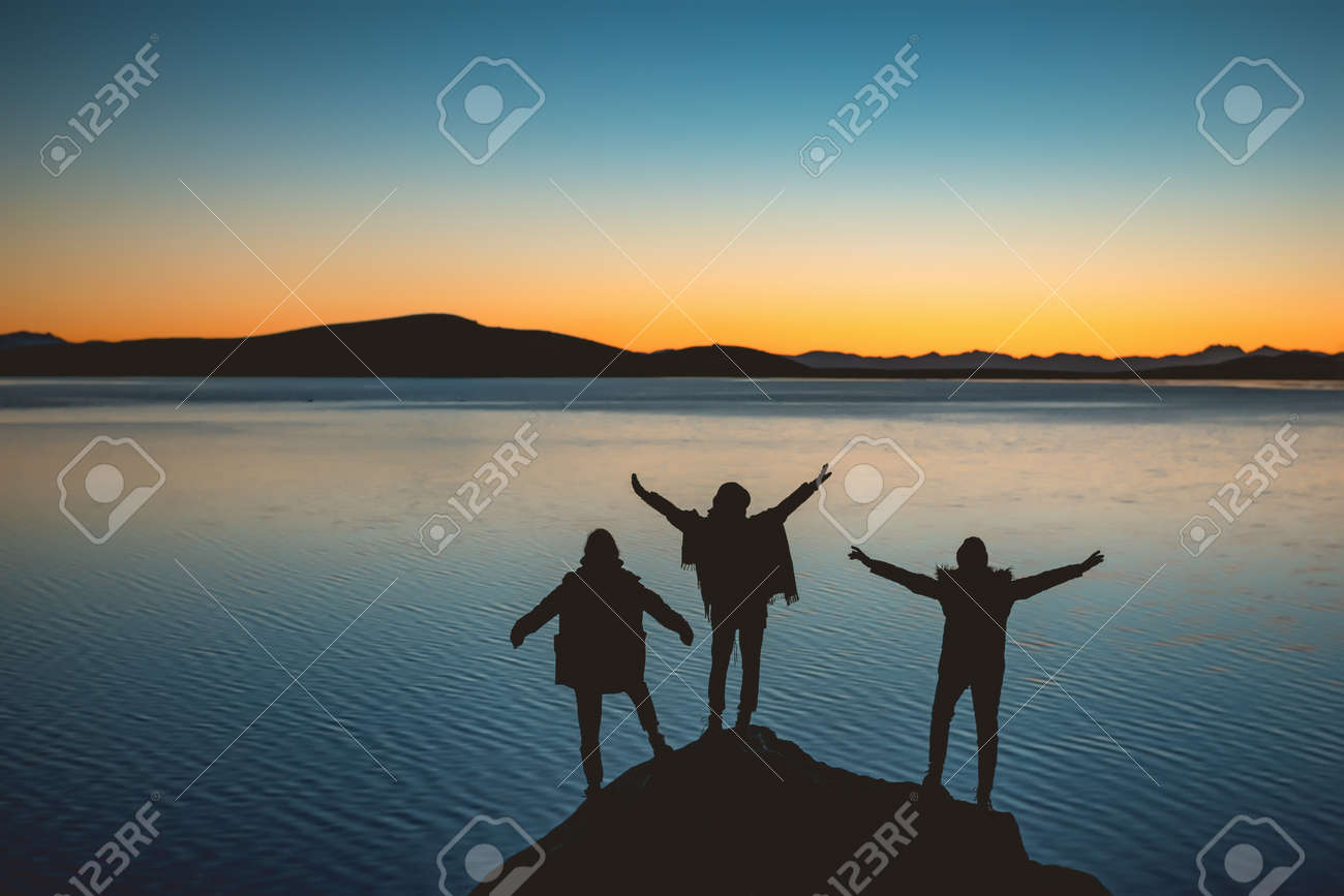 Silhouettes of three happy girls with raised arms stands against sunset lake and mountains - 159931401