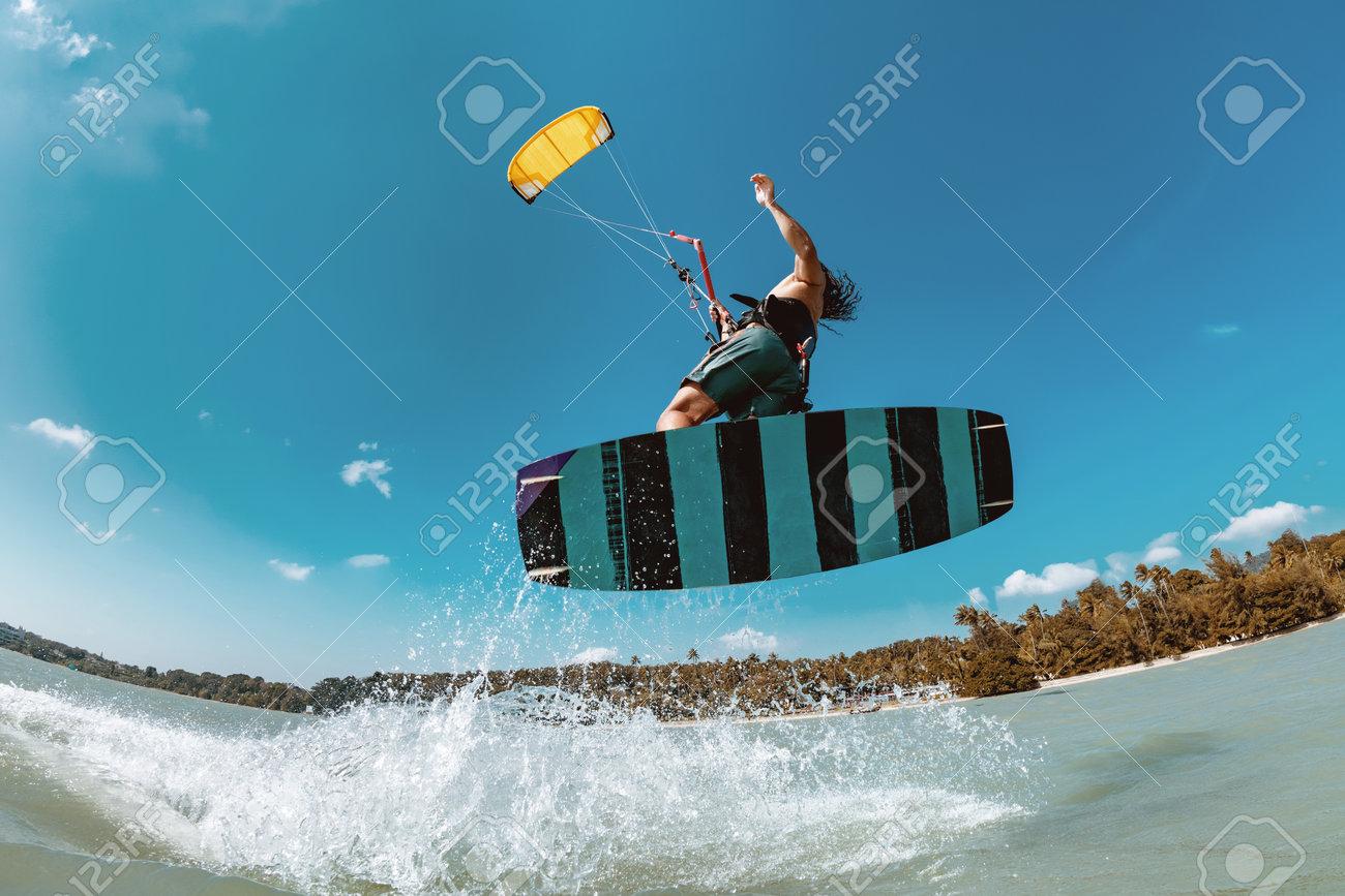Athlete wakeboarder jumps with kite at sea bay. Phuket island, Thailand - 162389384