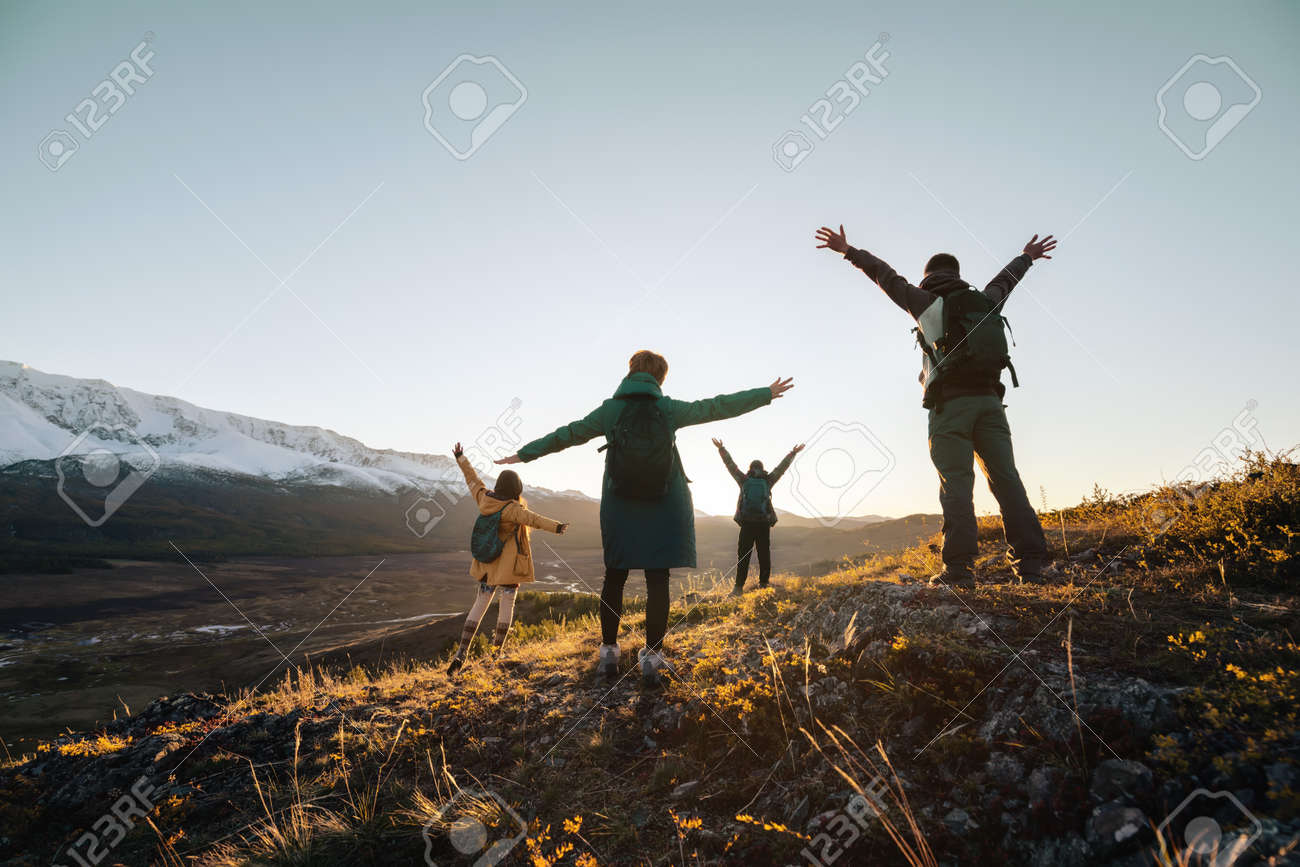 Happy hikers stands with raised arms and looking at sunset mountains - 163777778