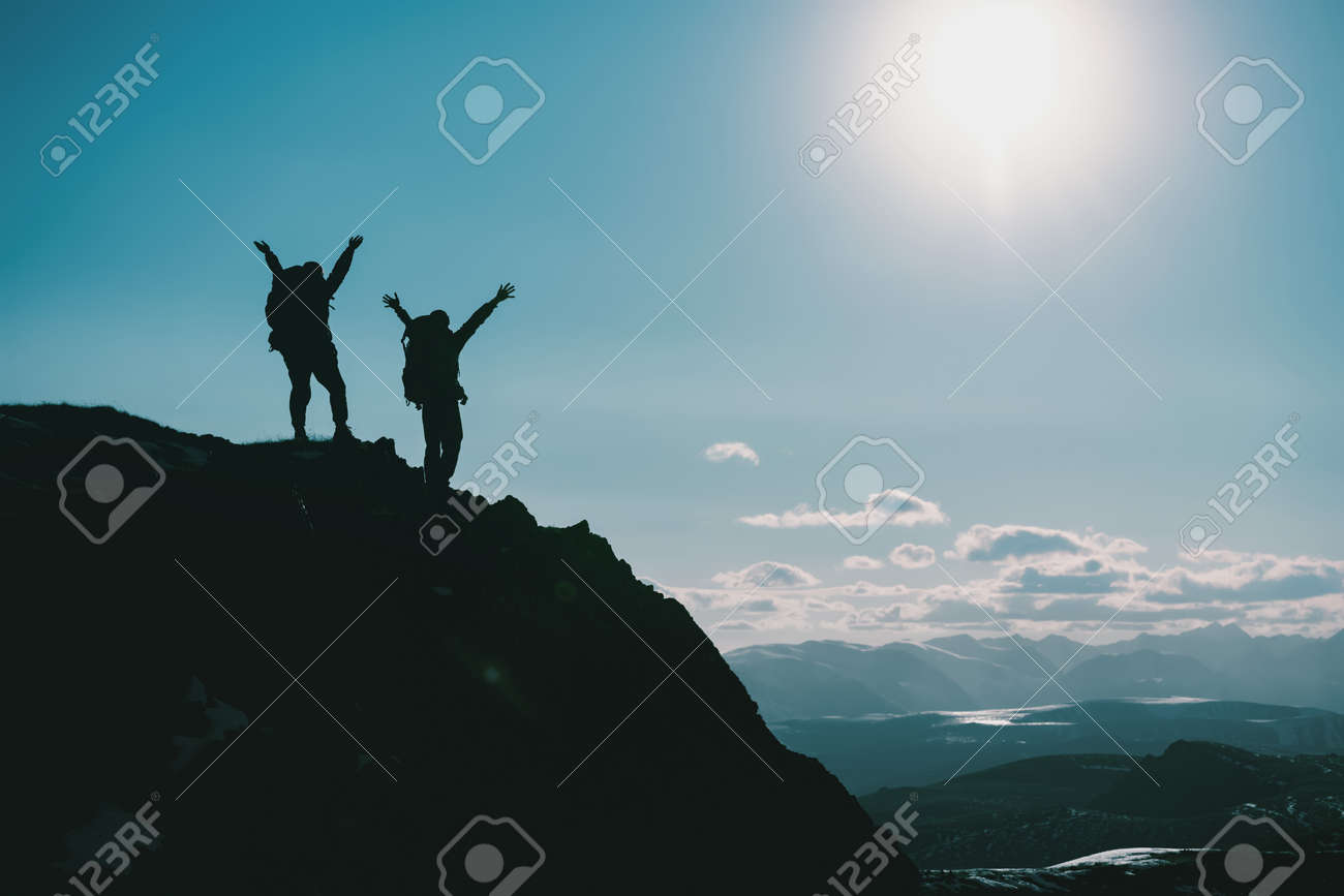 Silhouettes of two happy hikers in winner poses with raised arms are standing on mountain top - 163777781