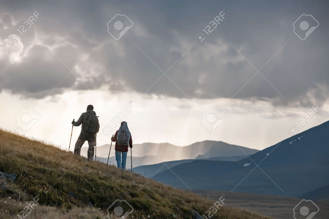 Two young hikers are standing on mountain slope against sunset rainy sky - 163964985