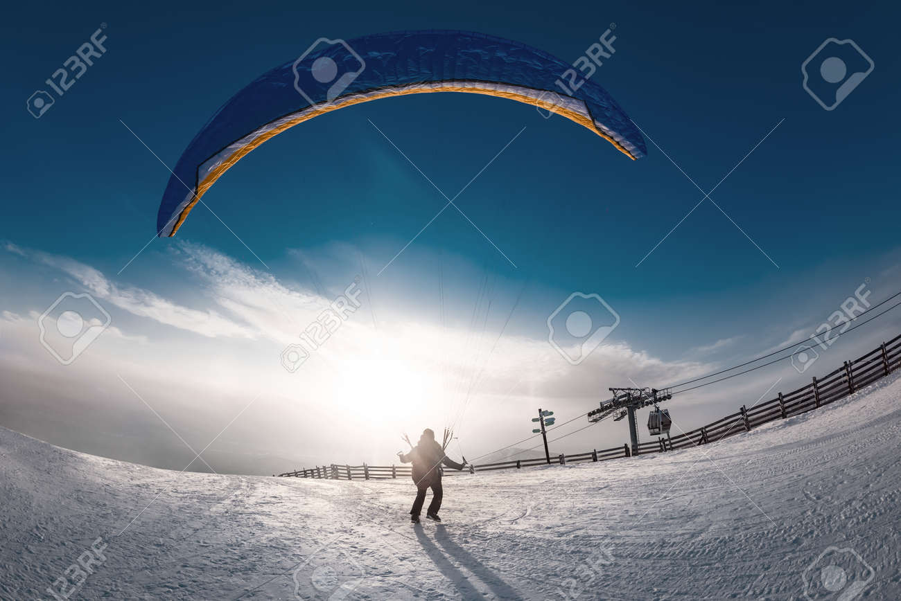 Lonely skydiver is taking off from mountain top at ski resort in sunset time. Sheregesh resort, Siberia, Russia - 165063005