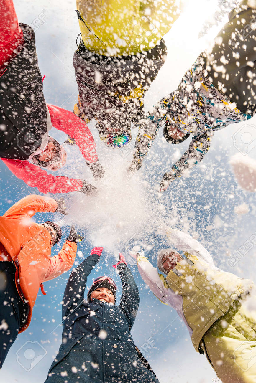 Group of happy friends at ski resort are having fun and throwing snow - 165275232