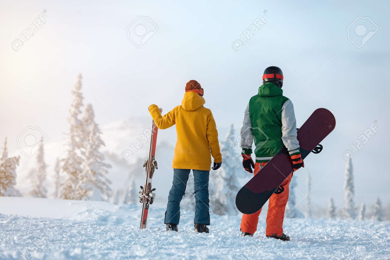 Female skier and male snowboarder are standing on background of snowcapped mountain at sunset time. Ski resort concept - 165555399