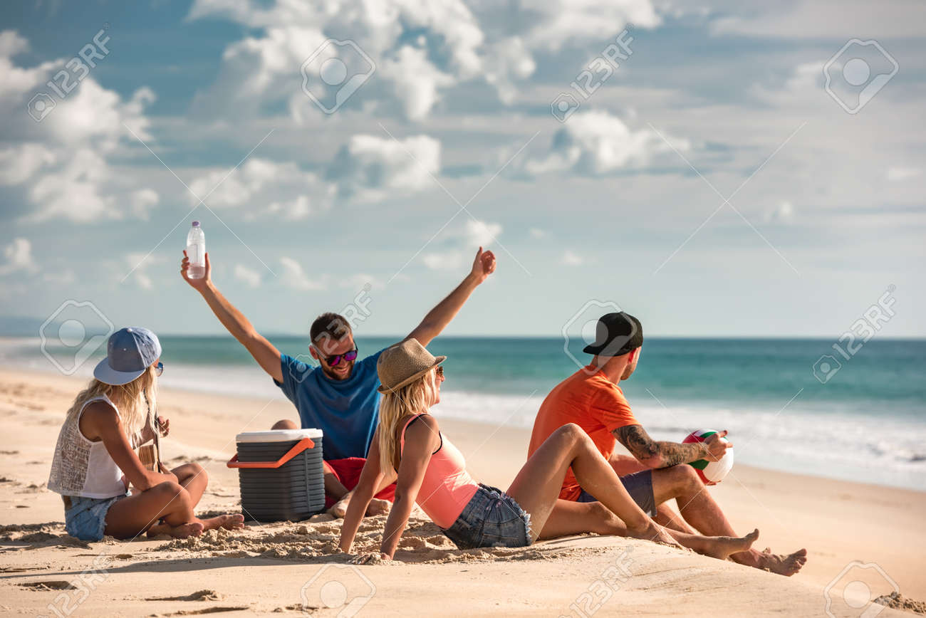 Group of friends are having fun and relaxing at sea beach picnic - 165561397