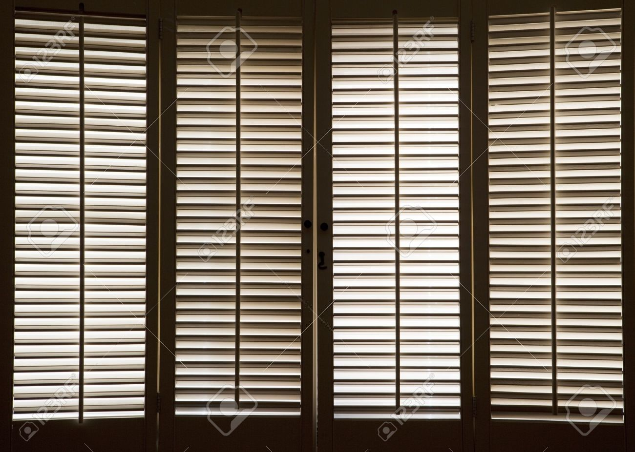 Wooden shutters in front of bright, sunlit windows - 12275249