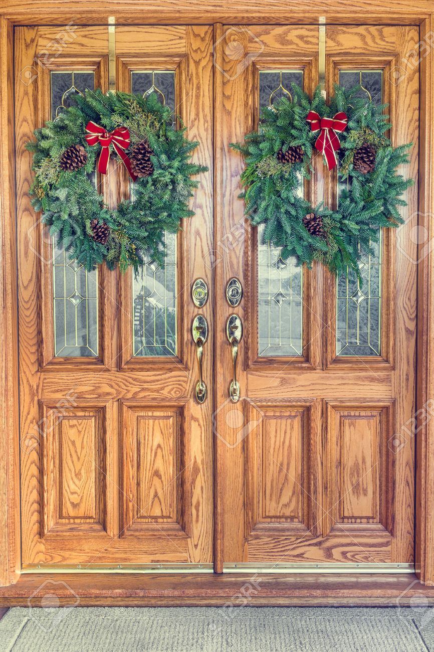 Stock Photo   Two Christmas Wreaths Hanging From A Double Front Door