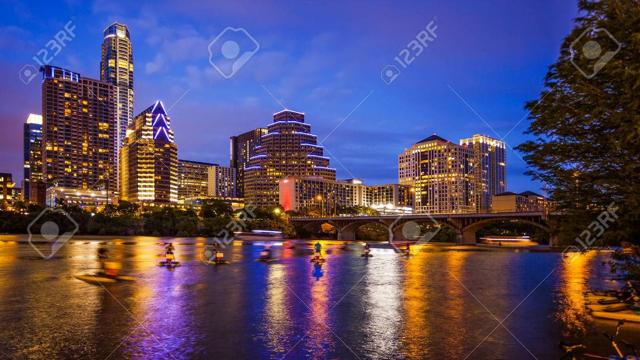 Austin, Texas downtown skyline at night on the Colorado River as unidentified tourists ride water bike's (All recognizable faces, building names and signs have been blurred for commercial use) - 58074933