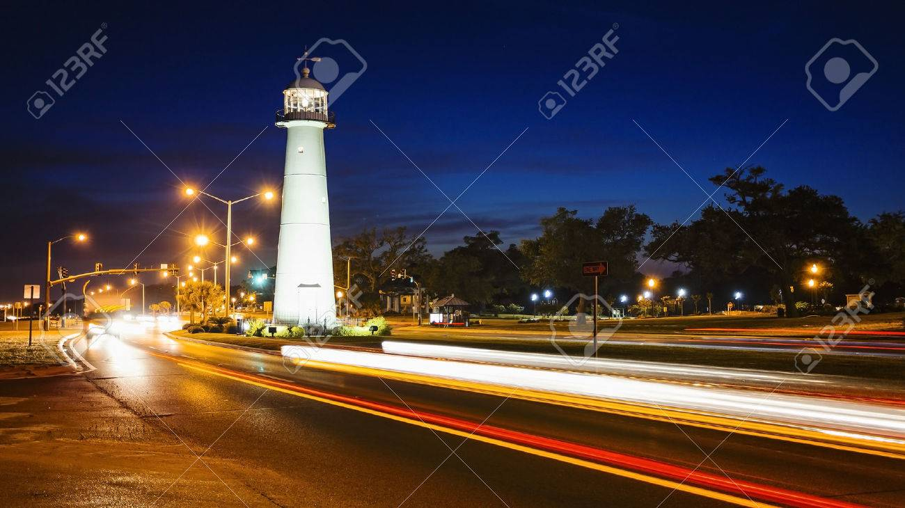 Biloxi lighthouse as night falls with passing automobile traffic in Mississippi - 65237964