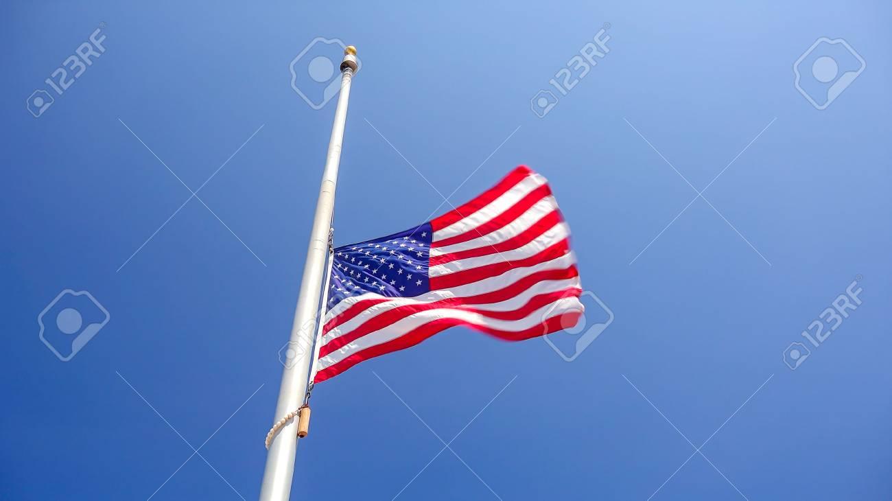 American flag flying at half mast aka half staff against a clear blue sky - 85878322