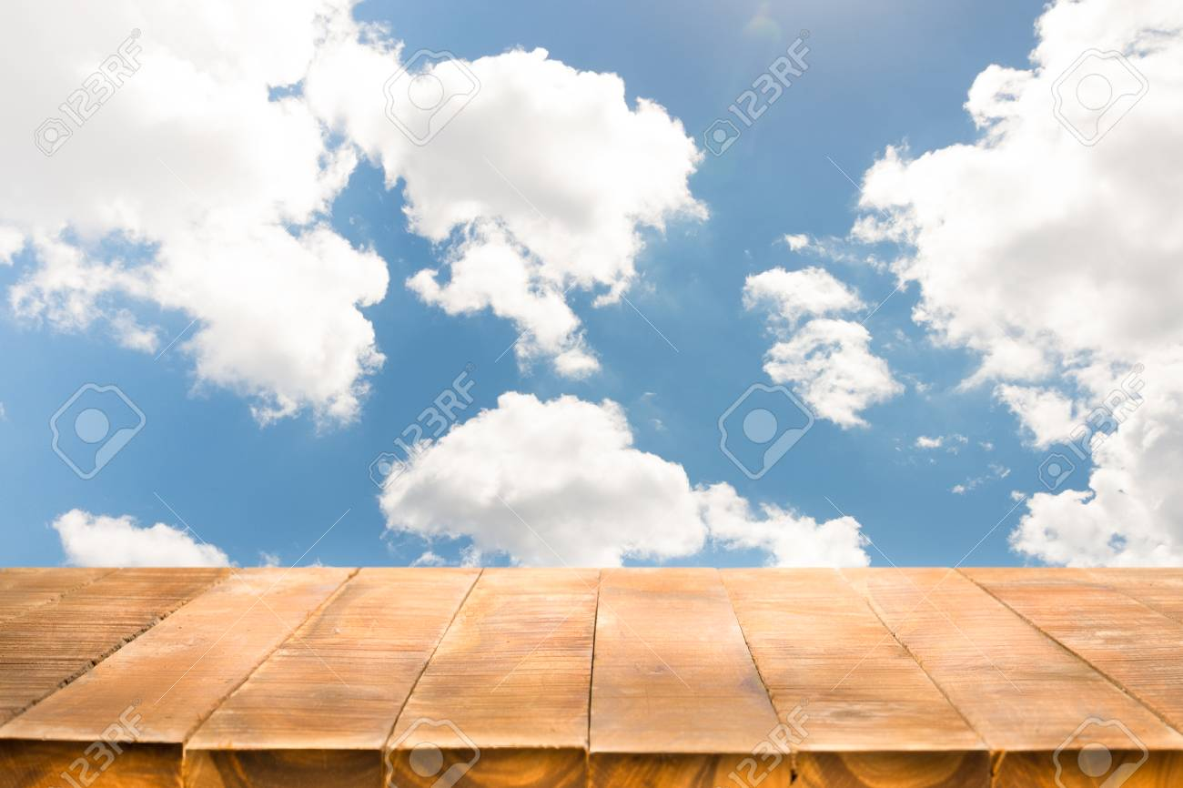 Empty of wooden table with perspective and bright cloudy sky