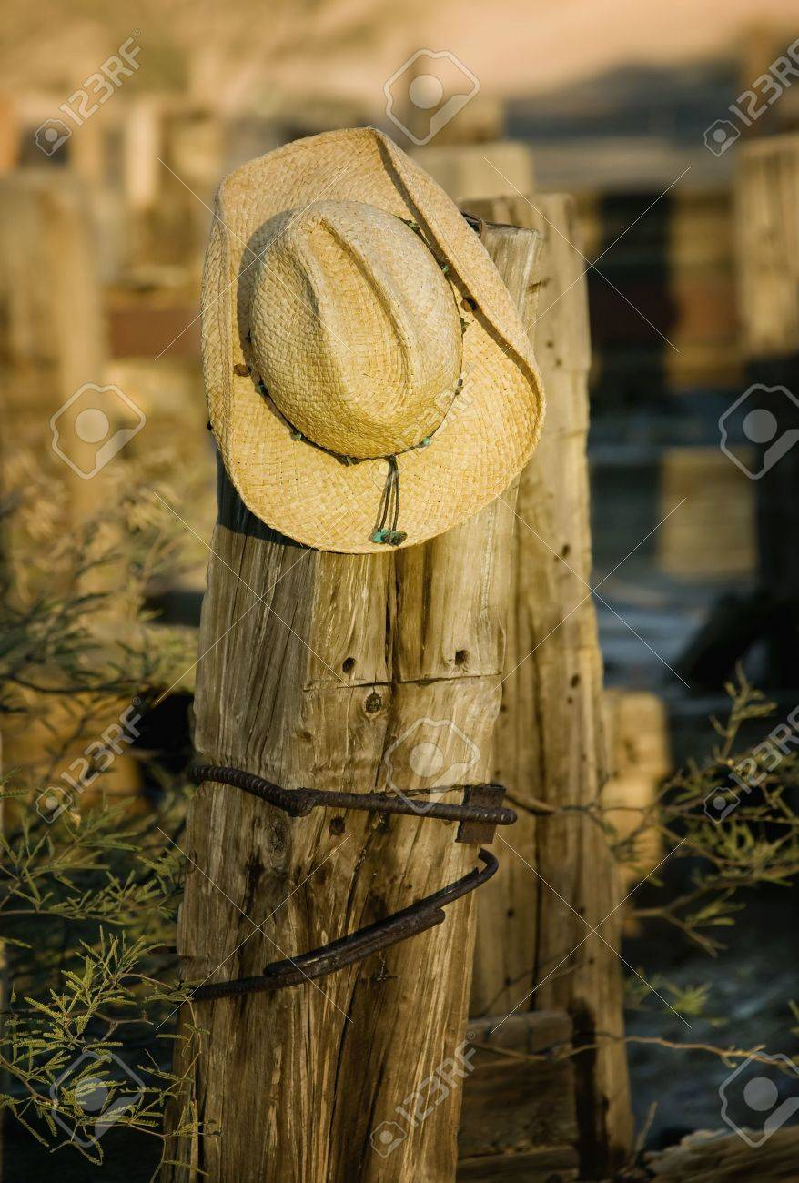 93b1122556b Stock Photo - Straw cowboy hat hanging on an old wooden post.