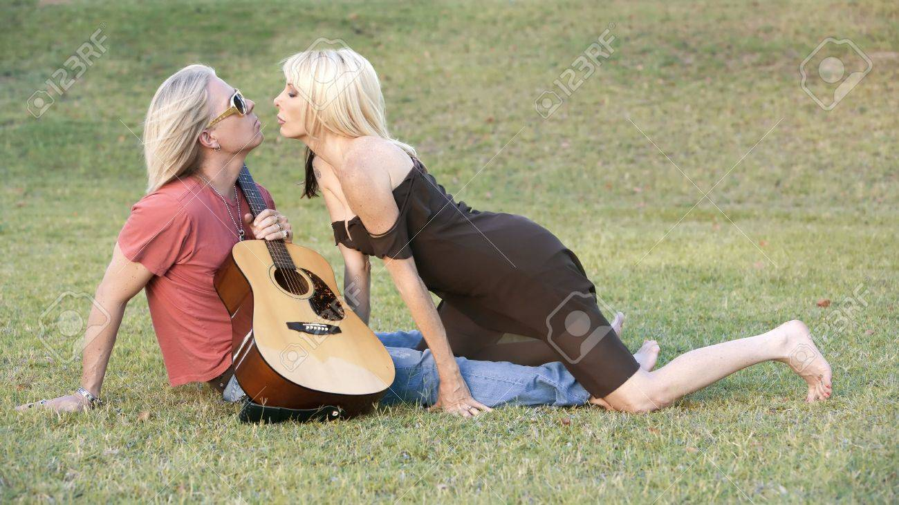 Hip Adult Couple With A Guitar Outside On Grass Stock Photo