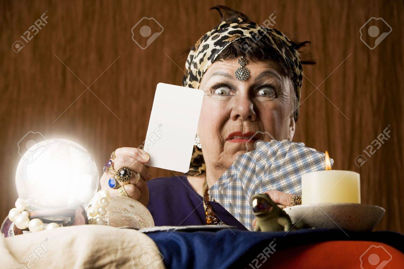 Gypsy fortune teller with crystal ball holding a blank tarot