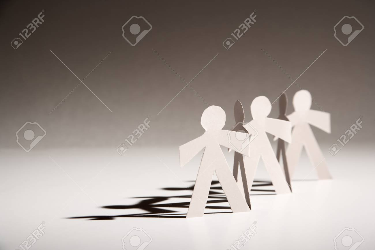 Line Of Cutout Paper Dolls Throwing A Shadow Stock Photo Picture