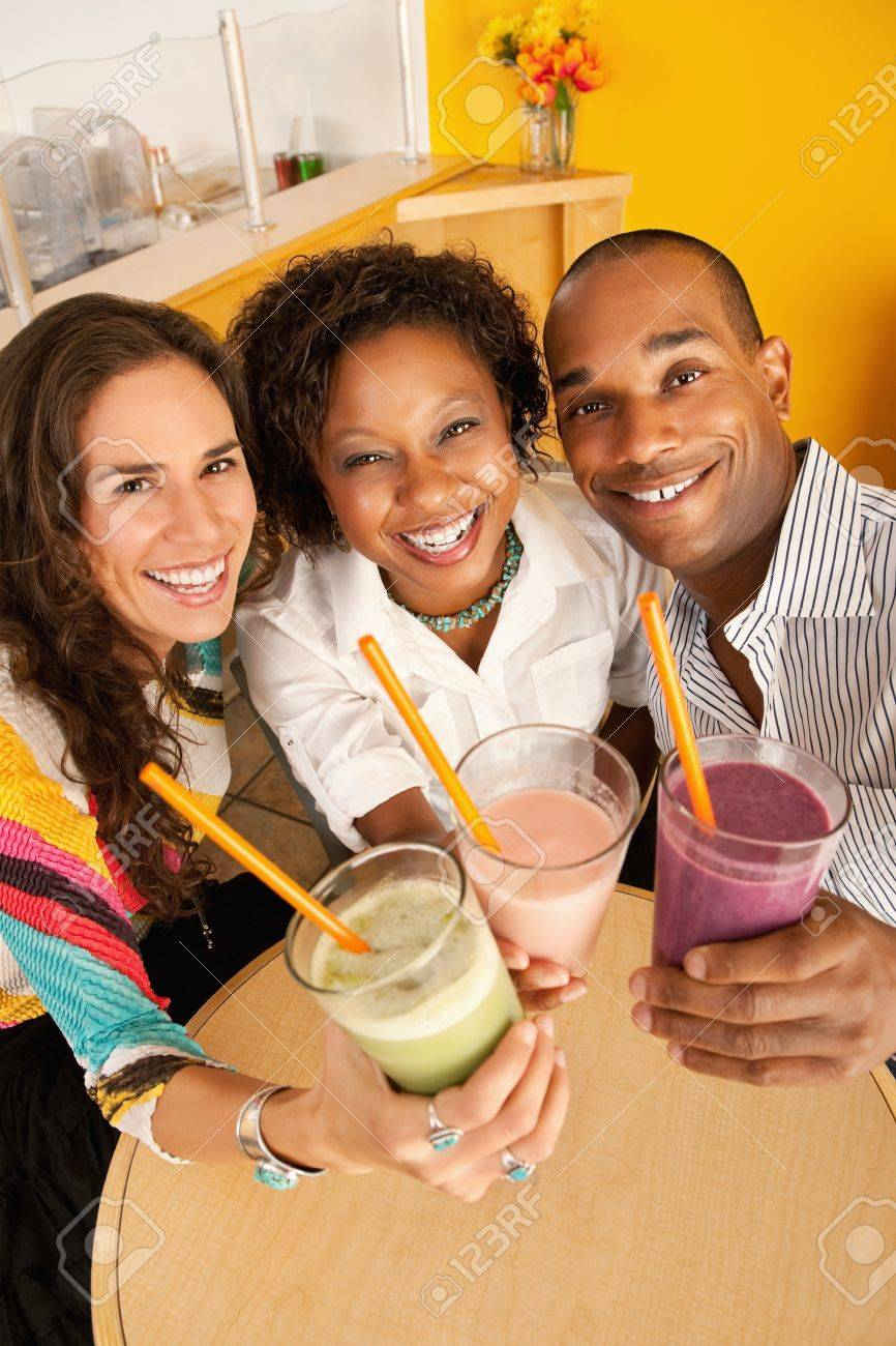 High angle view of three people at a cafe drinking frozen beverages. Vertical shot. Stock Photo - 7214419