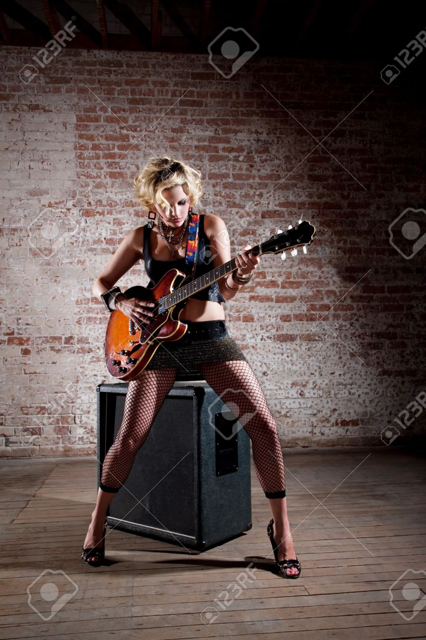 Female punk rock guitarist alone in a warehouse with a large speaker Stock Photo - 7244439