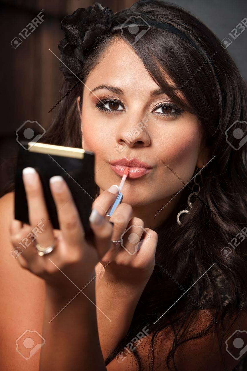 Beautiful Latina Woman Looking Into Compact Mirror And Applying Lip Gloss Stock Photo 8114312