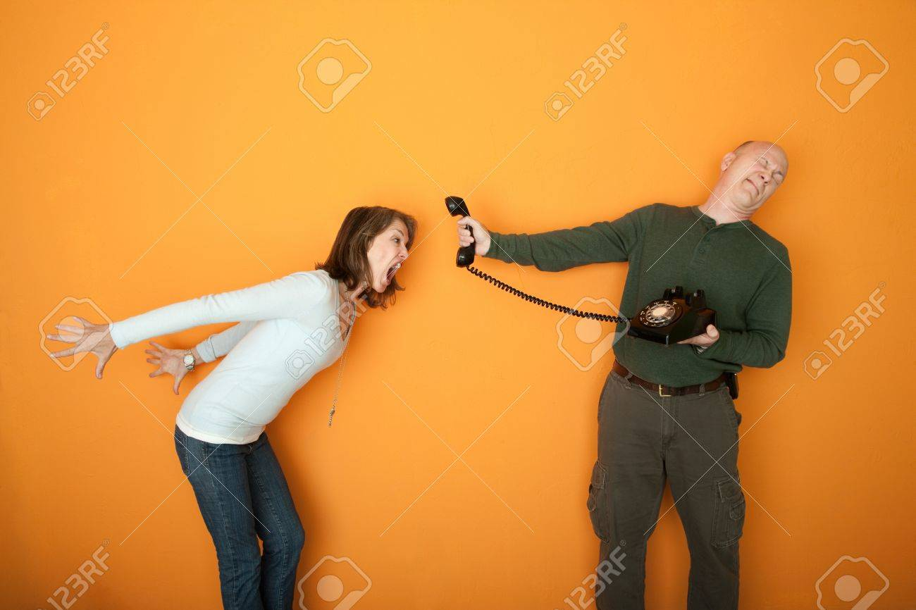 Man holds telephone while angry woman shouts into it Stock Photo - 9136910