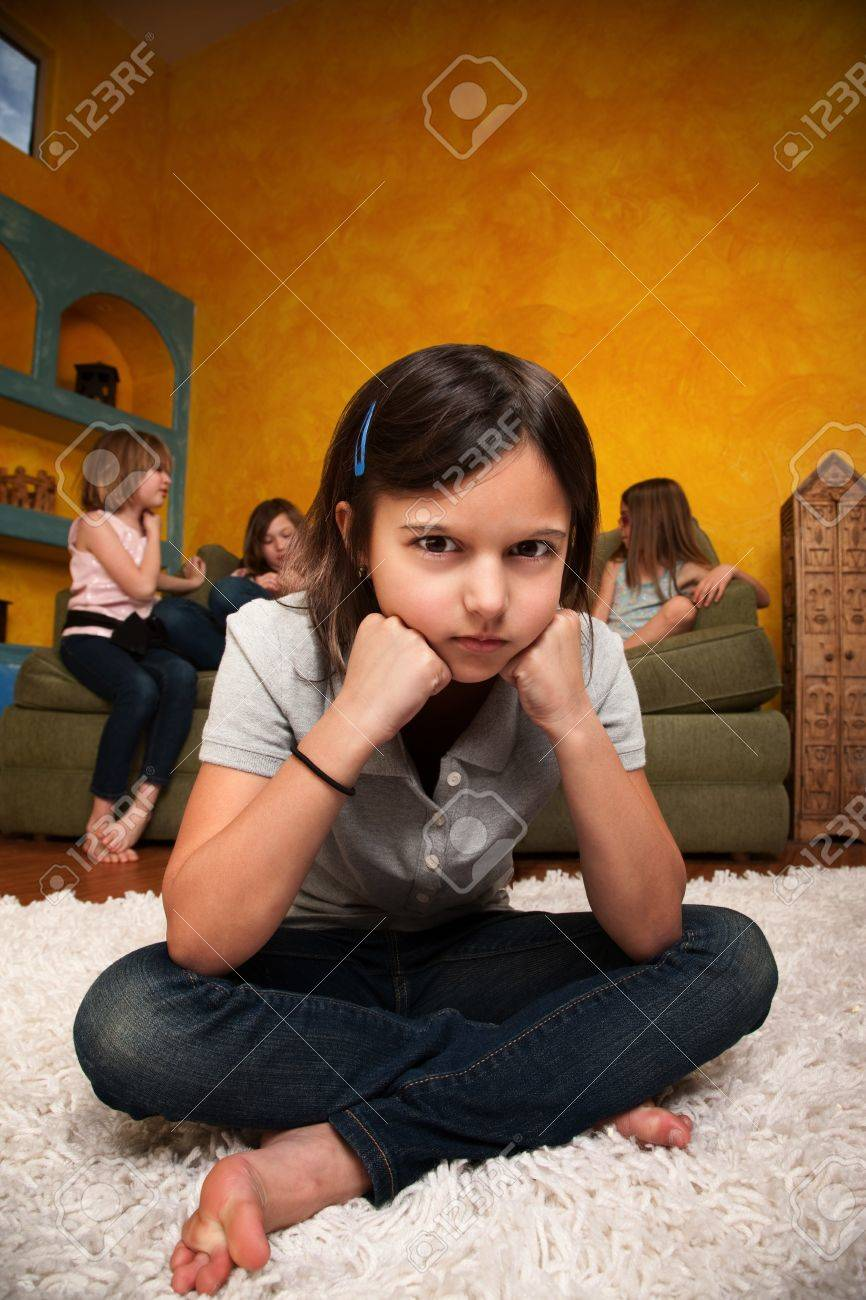 Sad little girl sits away from her friends Stock Photo - 9136913