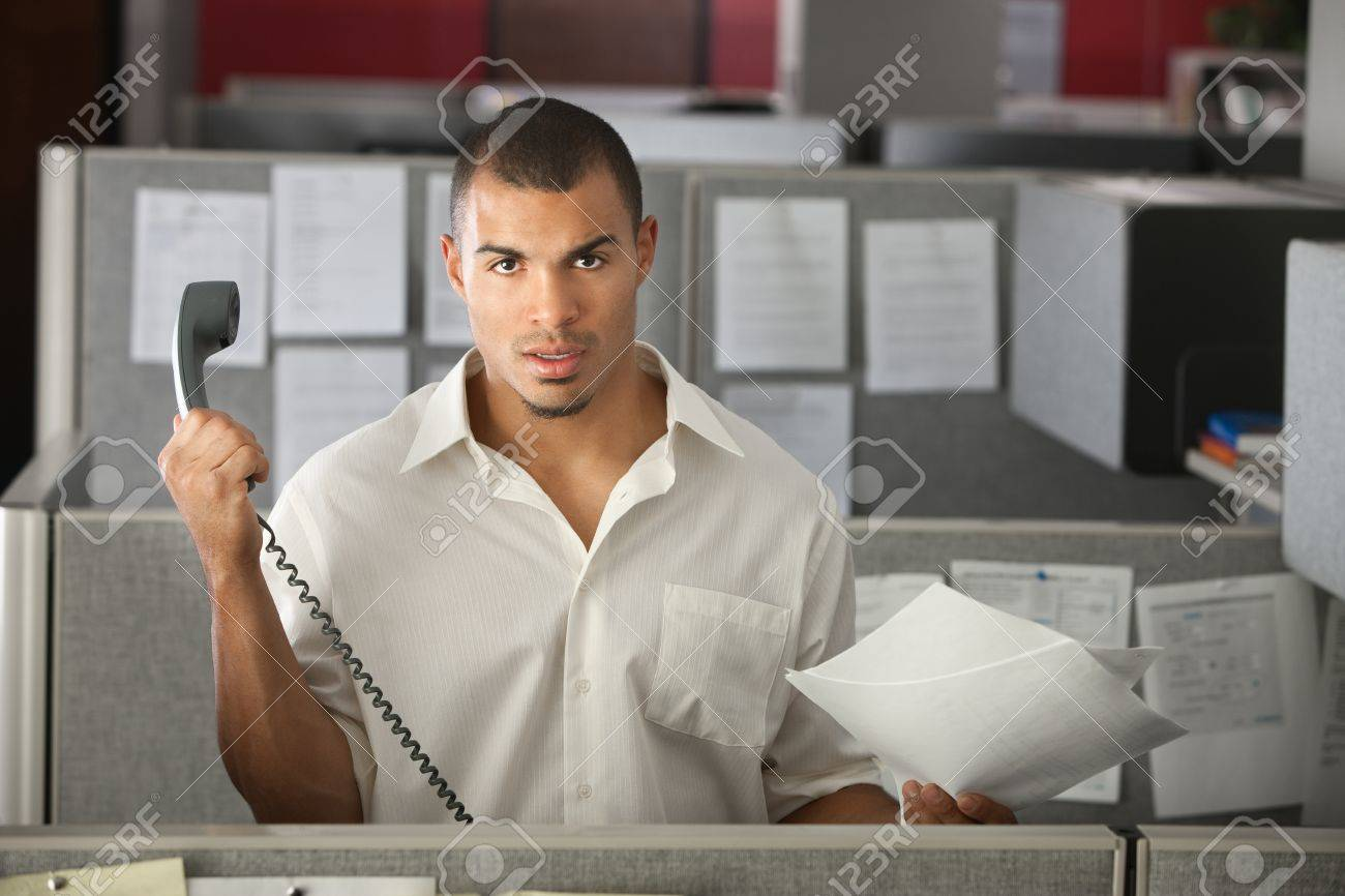 Frustrated office worker on the phone holding stock photo image - Frustrated Office Worker With Papers Holds A Phone Away From His Ear Stock Photo 9960963