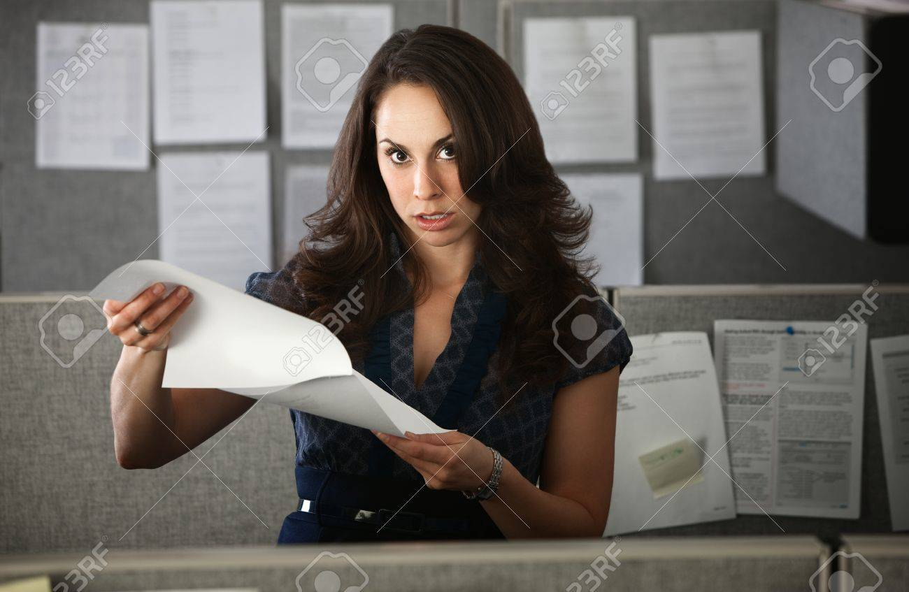 Frustrated office worker on the phone holding stock photo image - Frustrated Woman Office Worker Holding Documents Stands In Cubicle Stock Photo 9961026