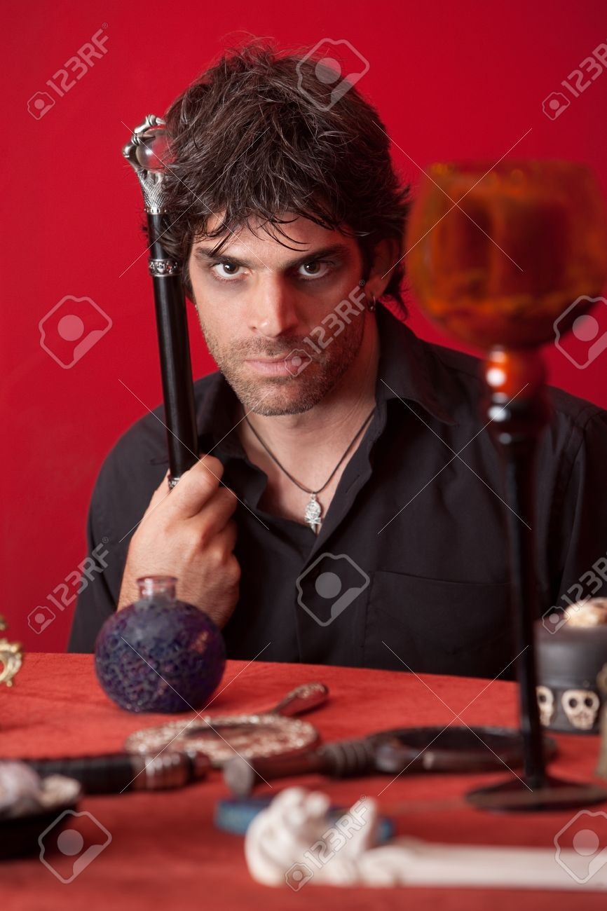Wizard with sceptre and magical objects over maroon background Stock Photo - 10553202