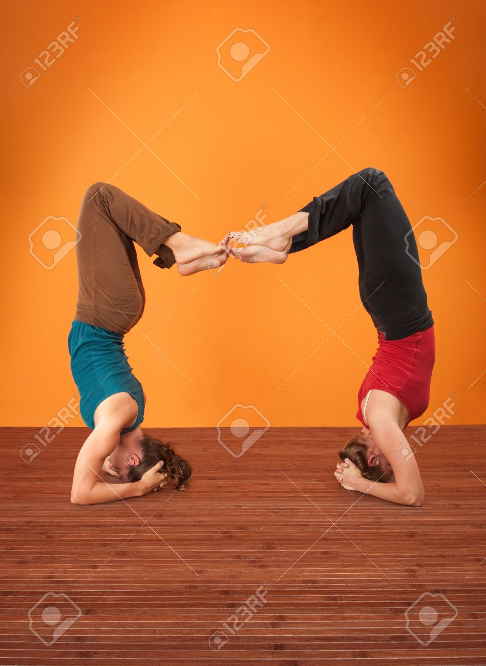 Two Women Perform Vrisikasana Yoga Posture On A Wooden Mat Stock