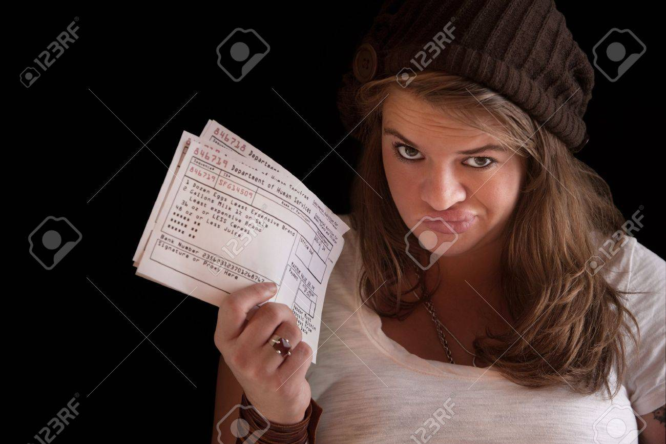 Unhappy woman with welfare food coupons over dark background Stock Photo - 12923525