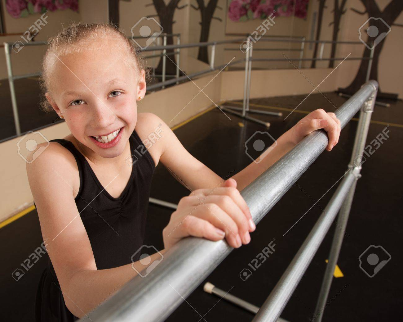 Young smiling ballet student holds railing in dance studio Stock Photo - 13649396