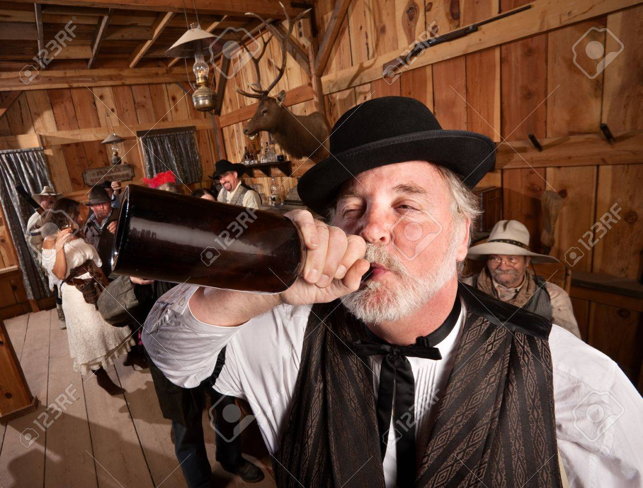 Drunken man chugs a bottle of alcohol in a saloon Stock Photo - 13889227
