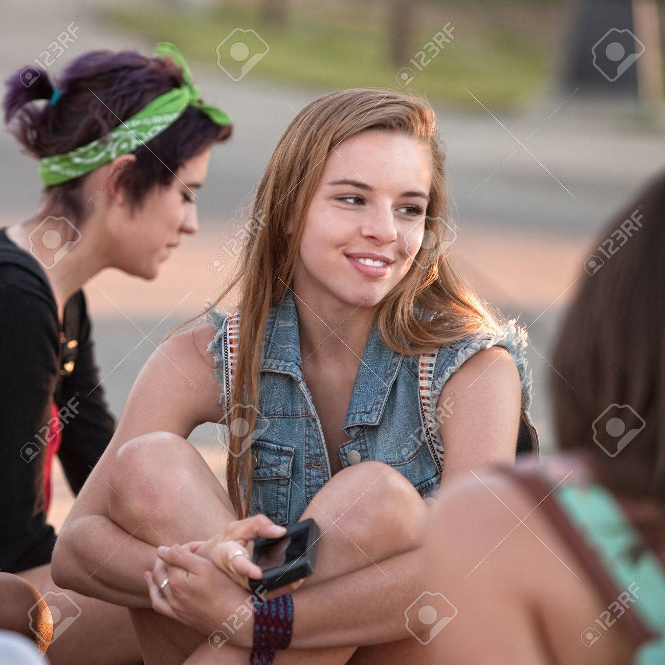 Pretty young teenage girl holding phone and smiling Stock Photo - 15433175
