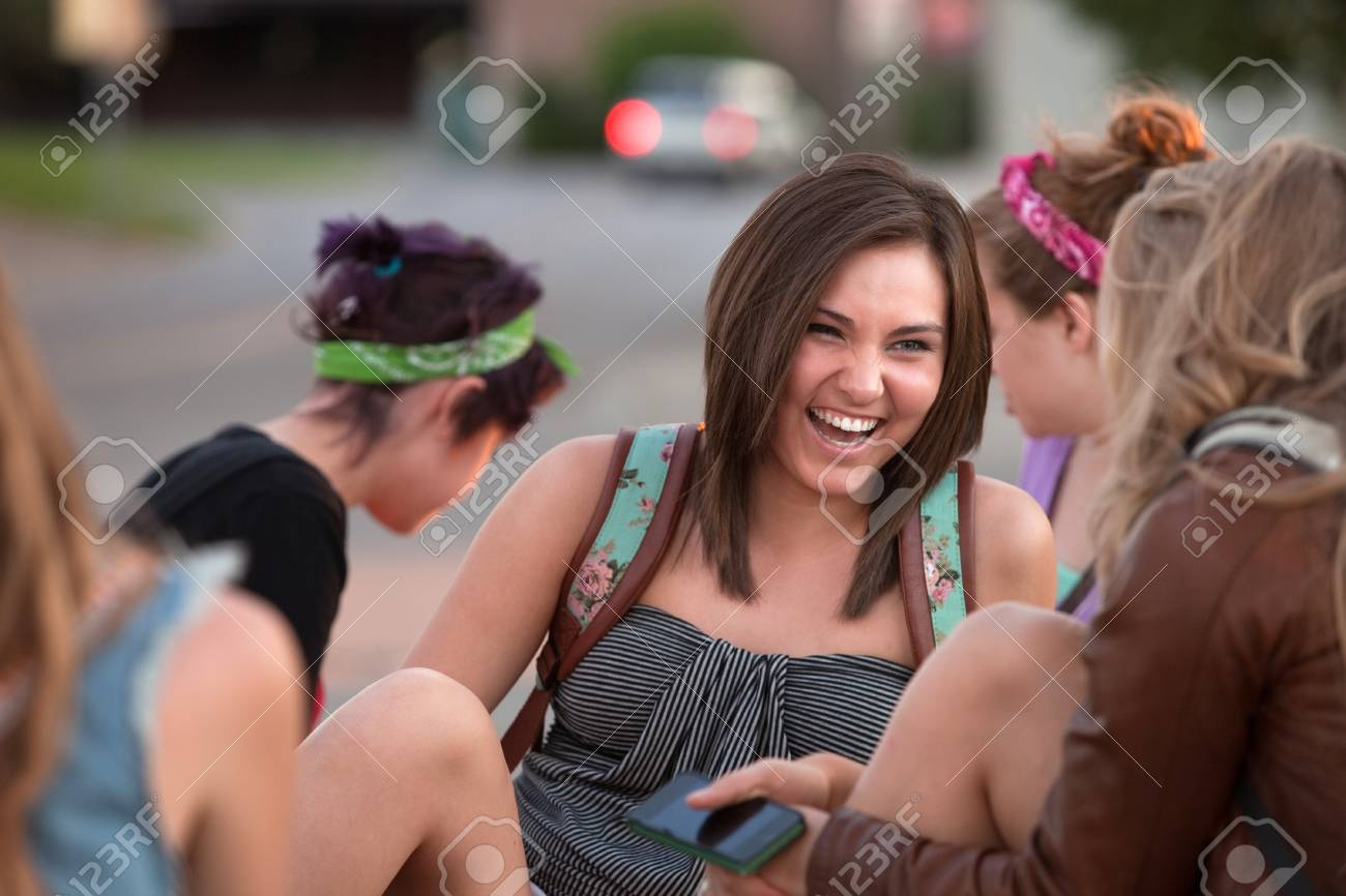 Beautiful teenage girl laughing with friends on campus Stock Photo - 15433140